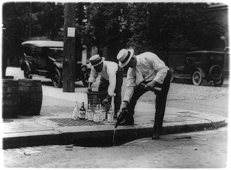 Men pour bottles into a storm drain