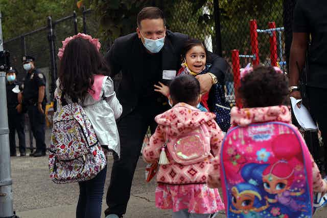 A mayor interacts with a group of schools girls wearing masks.
