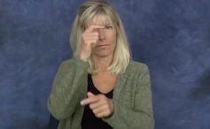 A woman holding her right hand to her eye and her left hand out in front of her with a pointed finger