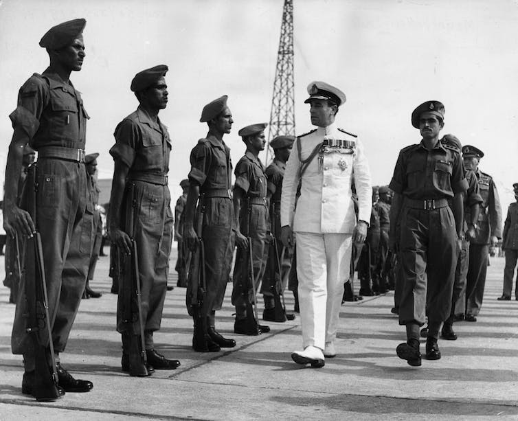 Black-and-white image of Indian soldiers saluting a British man in white military dress