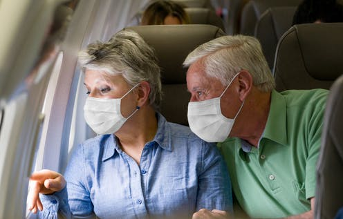 A older couple wearing masks in a airplane.
