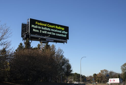 "A road sign that says ""Federal Court Ruling: Mail-in ballots received after Nov. 3 will not be counted!"""