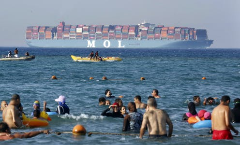 People bathe in the sea near an Egyptian beach as a large container ship passes by in the distance