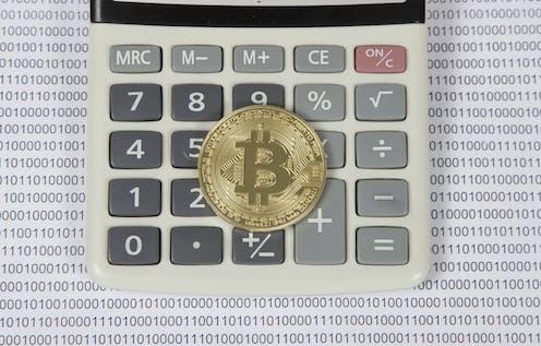 Bitcoin sobre el teclado de una calculadora.