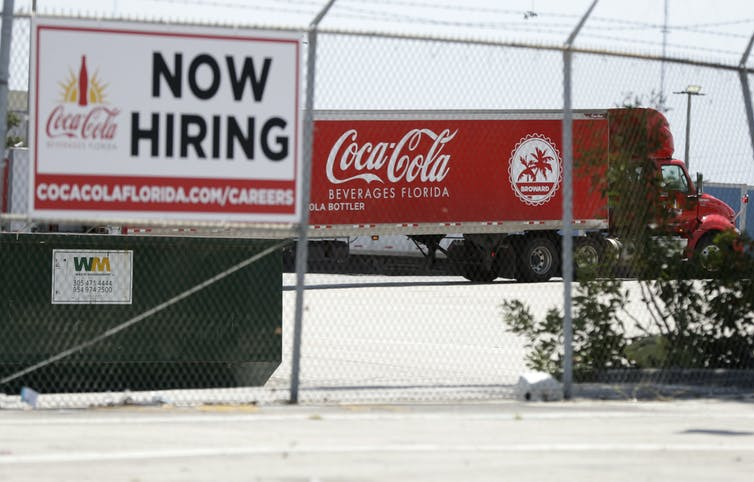 A tractor trailer truck backs into a loading dock at Coca-Cola Beverages Florida past a Now Hiring sign.