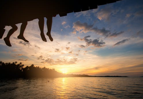 silhouette of legs dangling from a bridge at sunset over a lake
