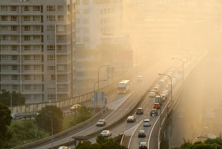 cars drive along a highway in a city masked by smog