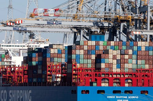 Giant shipping containers stacked on 10 high on a ship at a port