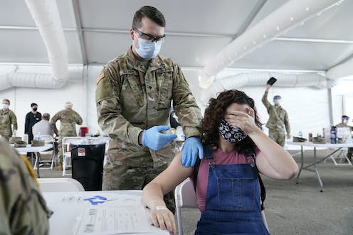 A Florida woman covers her eyes as she receives a COVID-19 vaccine shot