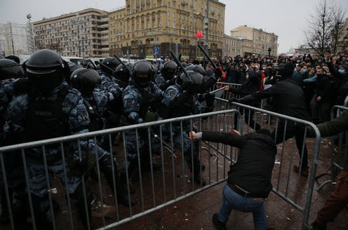 Crowd of policemen on the left dressed in riot gear and waving batons, confront a crowd of yelling people