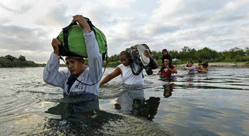 A group of migrants cross the Rio Grande River.