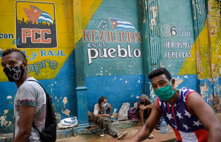 Cubans wearing face masks wait to buy food near a mural about the Cuban Communist Party and the Cuban Revolution.