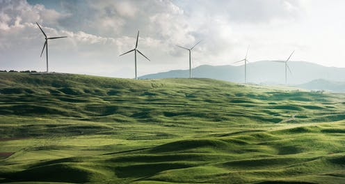 A hilly green field with wind turbines.