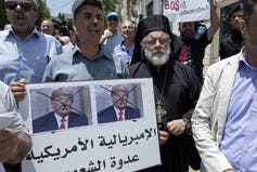 Activists from the Boycott, Divest and Sanctions (BDS) movement chant slogans and carry a placard with defaced pictures of former U.S. president Donald Trump and Arabic that reads: 'American Imperialism is the people's enemy.'