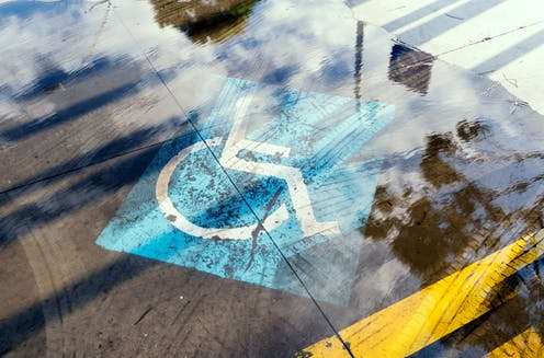 Floodwaters cover a disability sign on a parking spot.