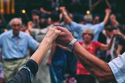 personas mayores bailan una sardana en la Plaza Nova de Barcelona.