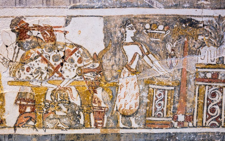 Priestess with hands outstretched over shallow bowl placed on an altar, to wash them with jug placed nearby.