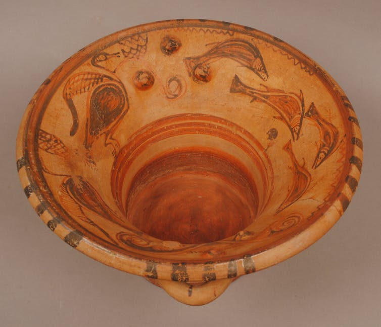 Clay hand washing bowl with fish and birds painted on the interior.