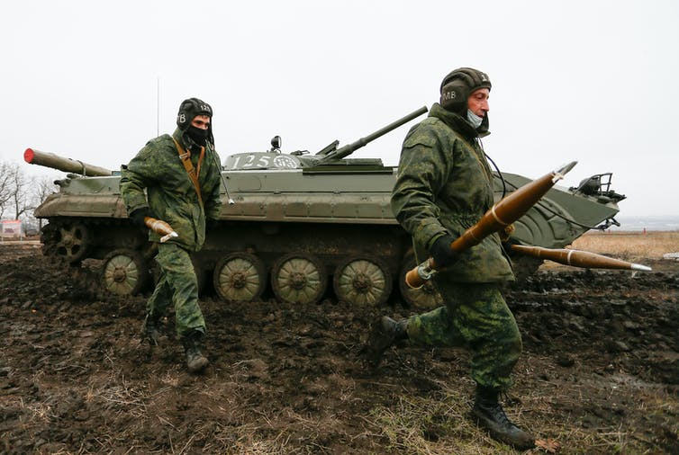 Two men in military uniforms carrying weapons with a Russian-made tank in the background.