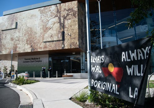A courthouse with a banner out the front that reads 'Always was, always will be Aboriginal land'