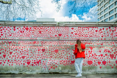 A visitor writes on a wall decorated with hearts in memory of the people who died of COVID-19 in the UK.