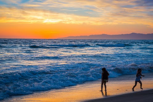 Children stand on the beach as the tide comes in at sunset.