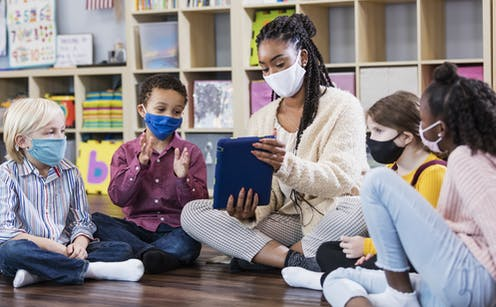 A group of students wearing masks surround a teacher who is also wearing a mask to look at a tablet.