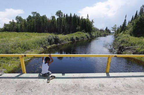 A boy sits on a bridge over a man-made channel in the First Nation of Shoal Lake 40 located in the northern boreal forest, straddling the Manitoba/Ontario border, in June 2015.