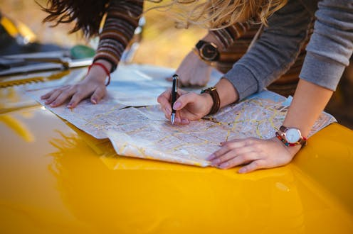 Two pairs of arms press a map down on the hood of a car. One hand holds a pen over the map.