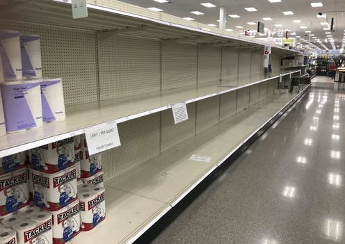 A few packages of paper towels sit on otherwise mostly empty shelves in a store
