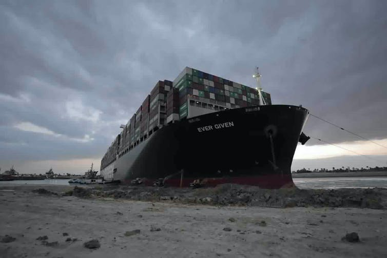 A large container ship known as the Ever Given is stuck in mud along the shore of the Suez Canal