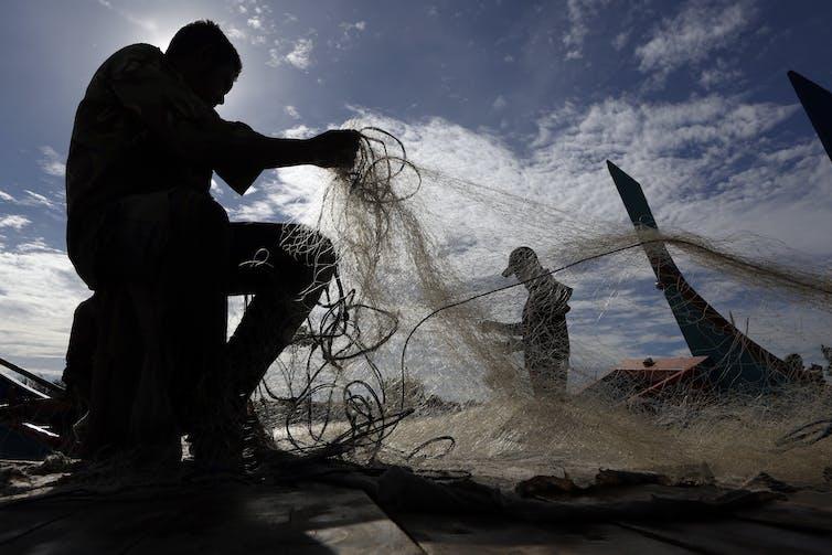 Men handle fishing nets