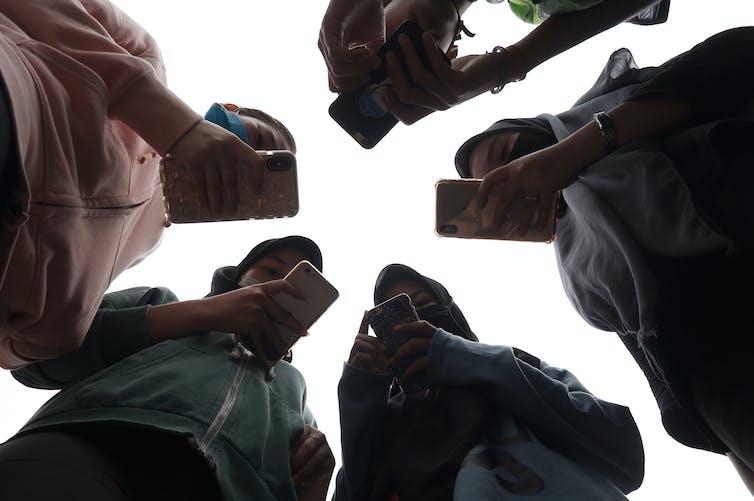 Sekelompok remaja menggunakan ponsel.