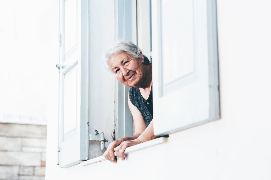 Old woman looking out of care home window