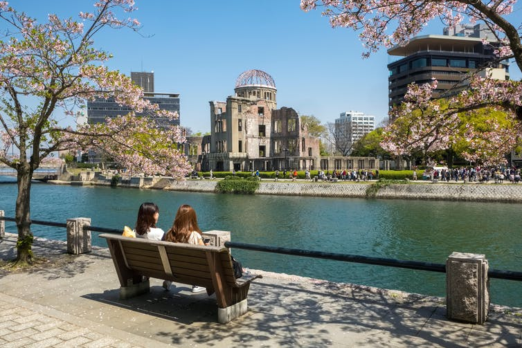 Tourists sitting on bench looking out onto river opposite the Hiroshima Peace Park in Japan
