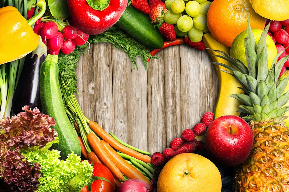 An assortment of fruits and vegetables collected in the shape of a heart.