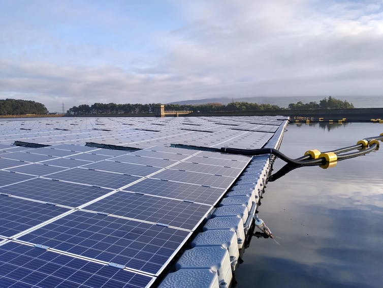 A raft of solar panels held in place on a reservoir's surface with a mooring rope.