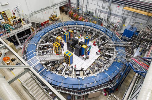 The muon experiment from above, showing a large blue ring surrounded by equipment.