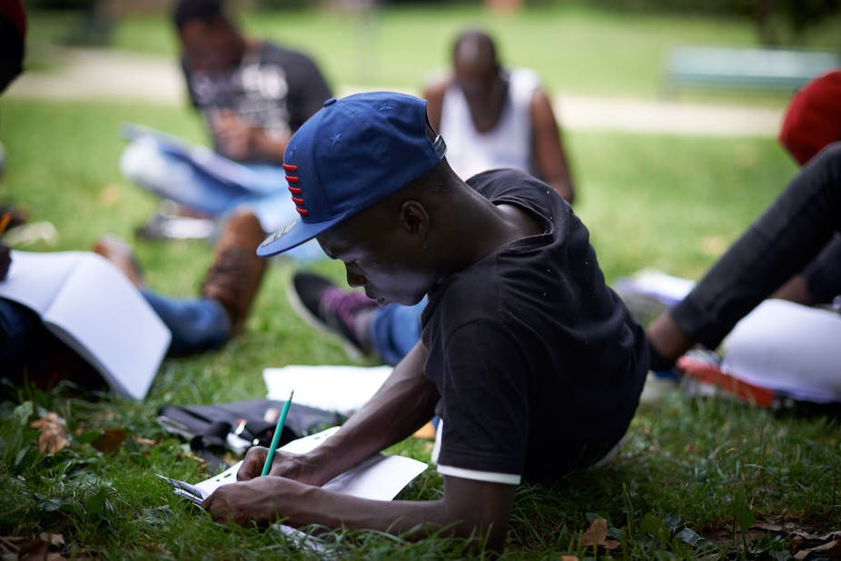 A young man writes in a book in a park