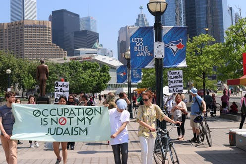 People carry a banner reading Occupation is not my Judaism.
