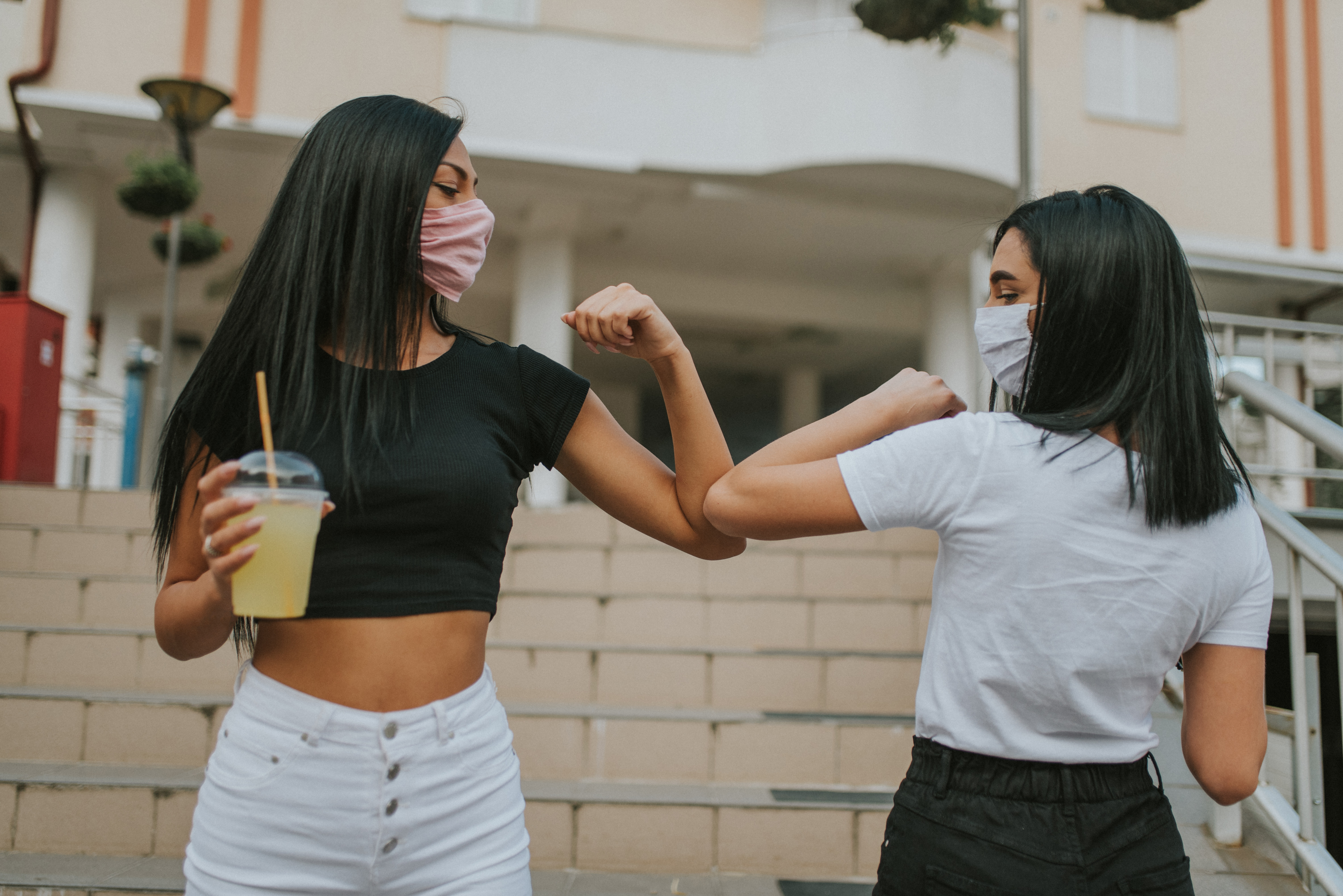 Two women wearing masks greet each other with elbow bumps.