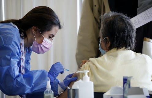 A nurse vaccinating a woman