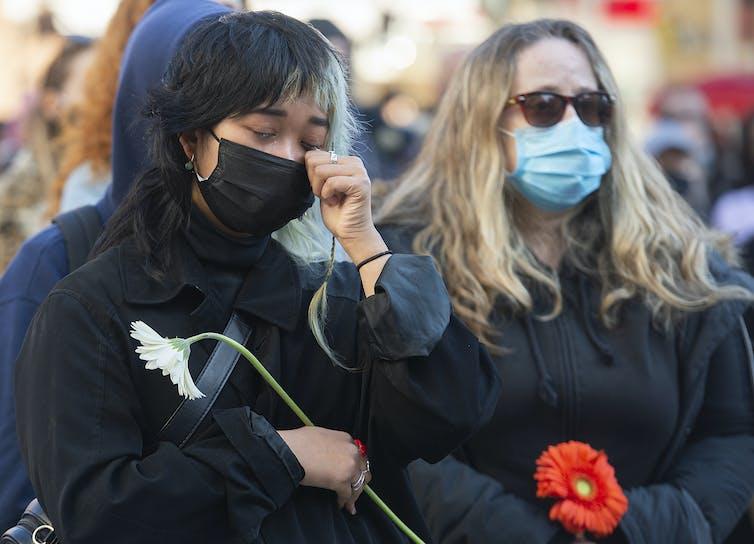 A woman sheds a tear holding a flower