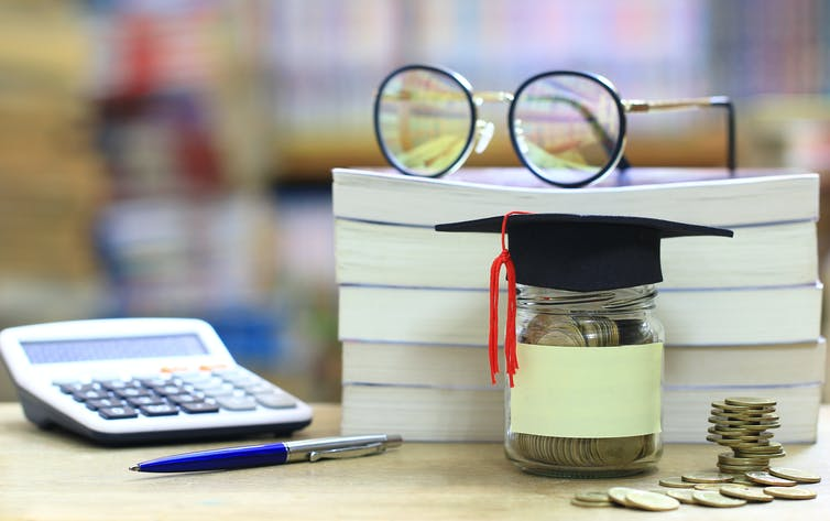 A pair of eye-glasses on top of a stack of three books.