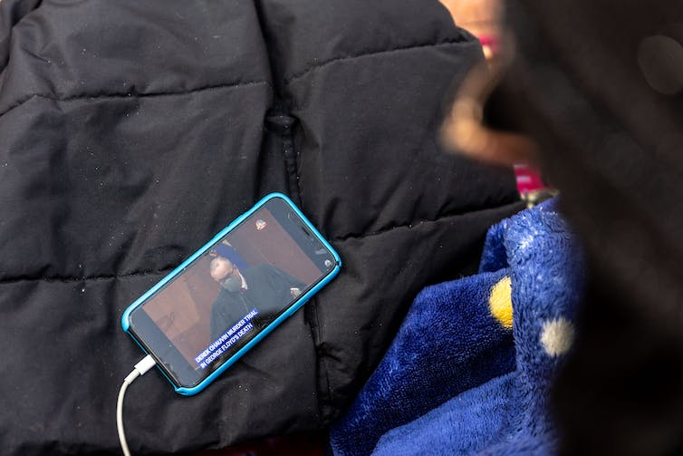 An activist watching the trial on a cellphone outside the government building in Minneapolis where the trial is taking place.