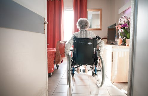 A woman in a wheelchair enters a bedroom at a nursing home.