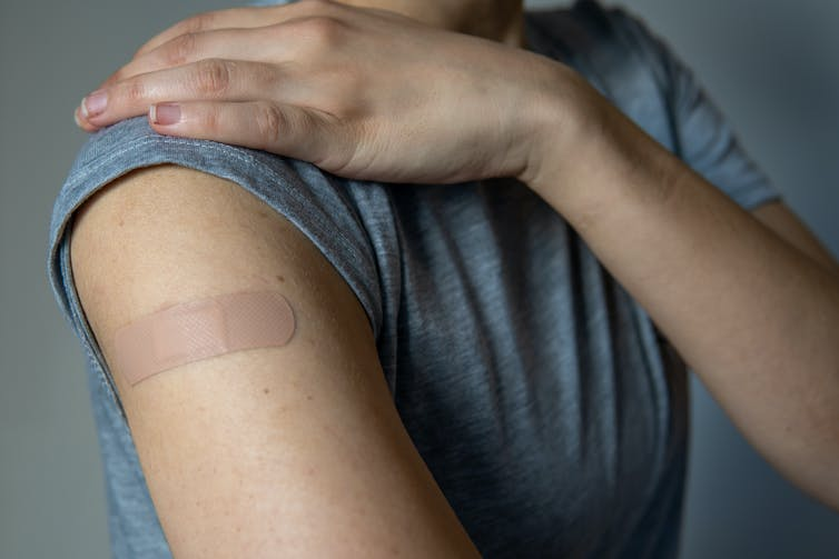An arm with a bandaid on the upper arm.