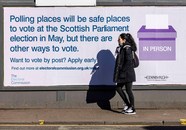 Woman walking past a poster about voting options for election