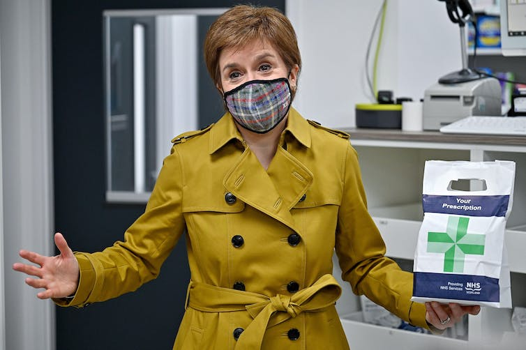 Nicola Sturgeon in a chemists holding up a prescription bag