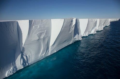 A towering ice shelf with deep-blue ocean water beneath.